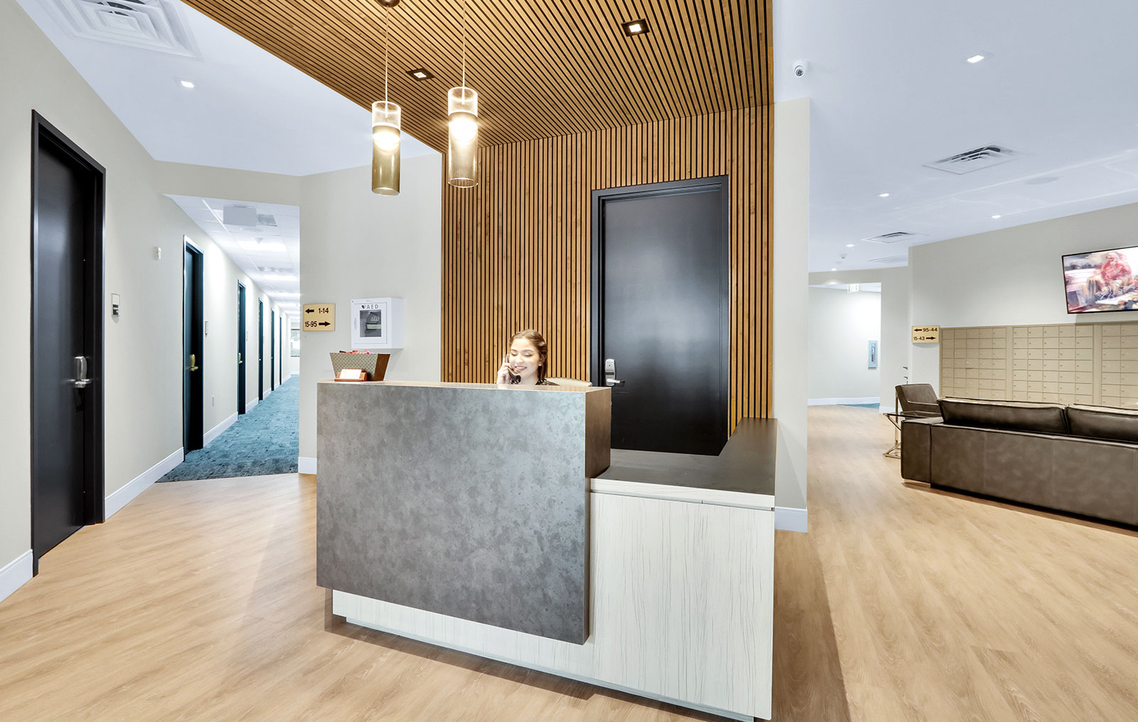 A reception desk with a receptionist taking calls with a hallway of offices to the left and the lounge like space of the mail room on the right