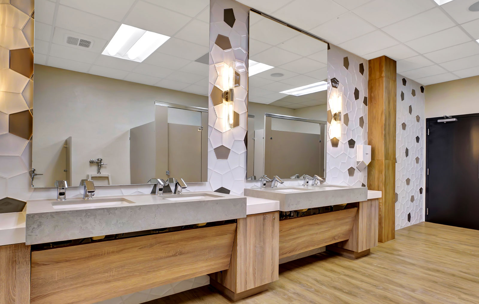 four sinks, grouped into two, with large mirrors per each group and small indented counter spaces buffering the sides of each group