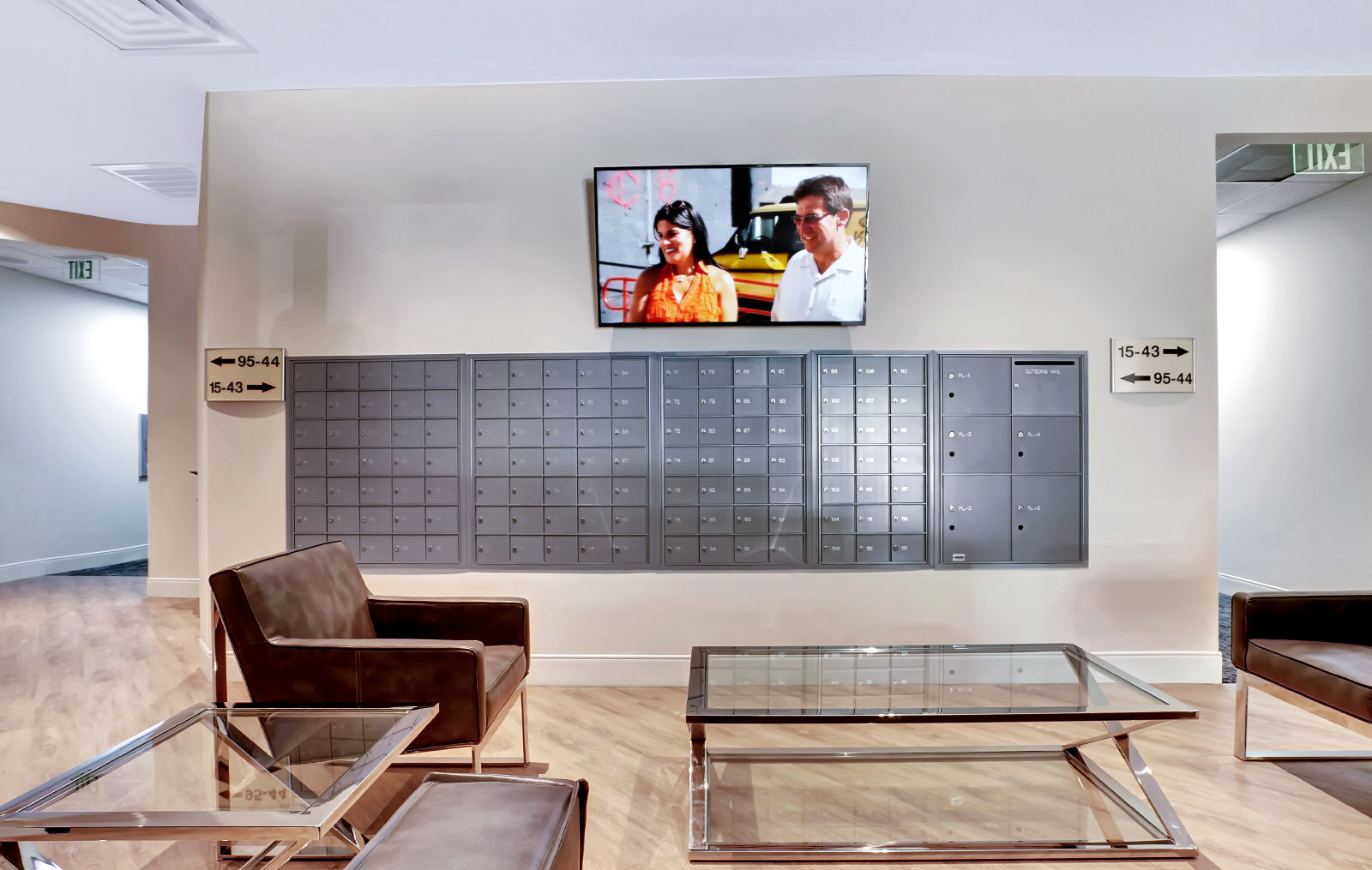 A wall of mailboxes with a flat-screen TV mounted above them, with cushioned chairs and glass coffee tables occupying the open space