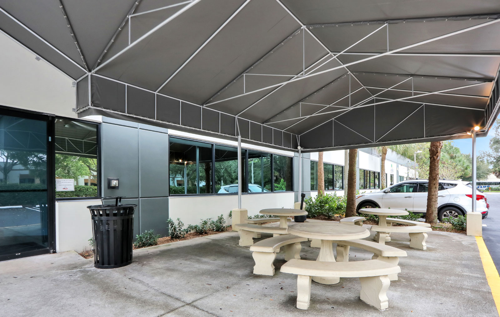 A large covered patio with three concrete circular tables that are accompanied by three curved concrete benches at each of them.