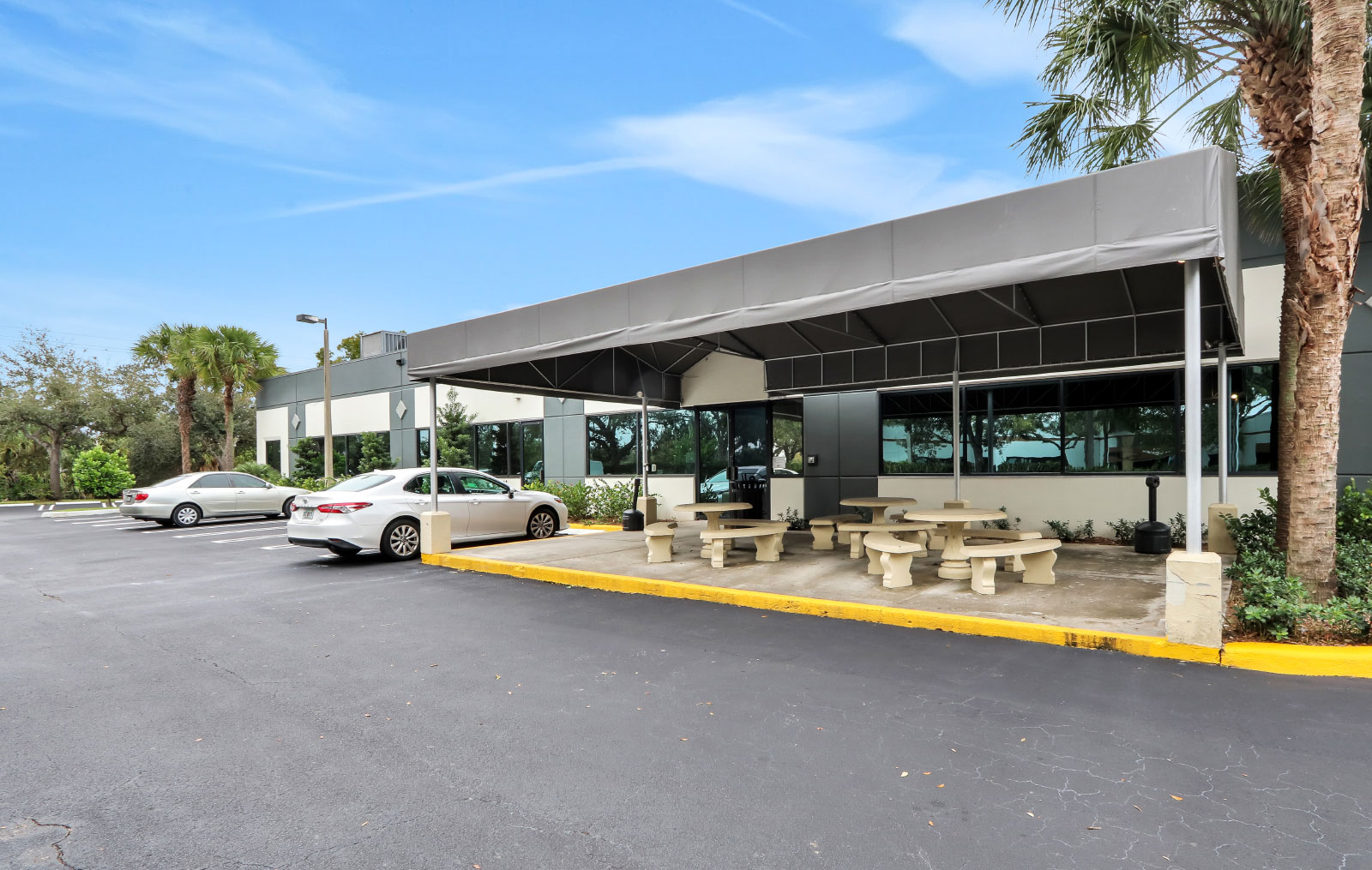 A view of the covered patio with concrete tables and benches with handicapped parking spaces to the left of it.